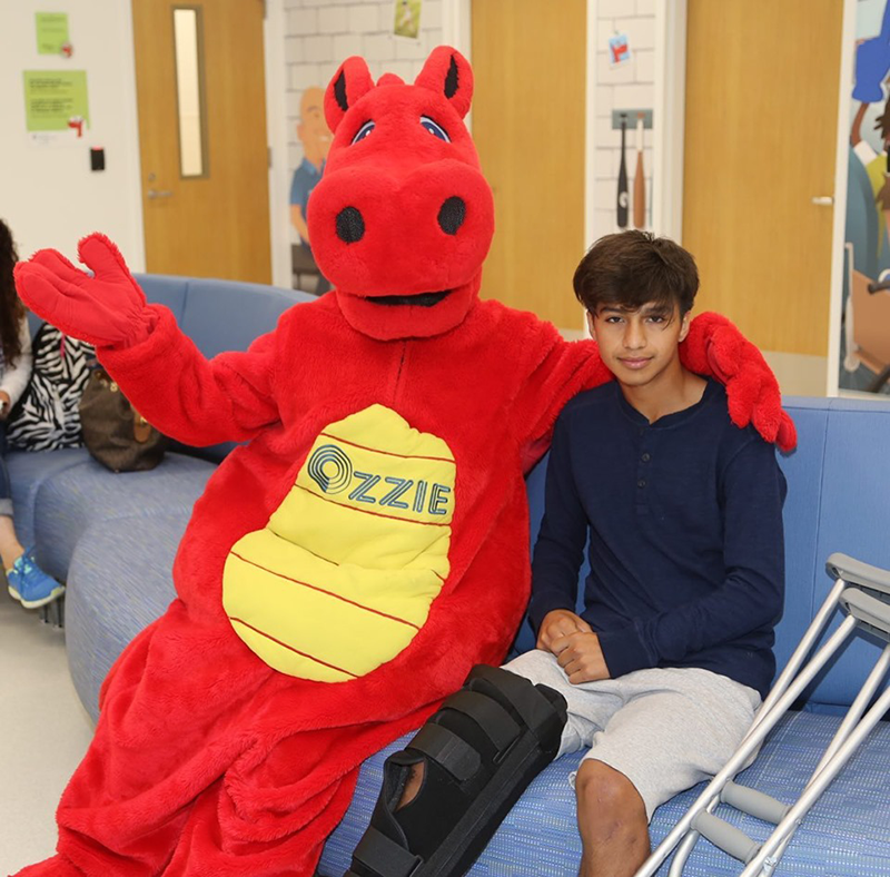 OIC's mascot Ozzie sits with the new Urgent Care Center's first patient, Bryan