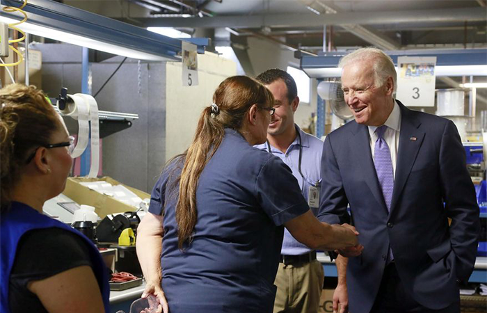 Vice President Joe Biden, right, greets worker Pamela Mesolella, left, during a visit at the Bobrick Washroom Equipment Factory in Los Angeles on Wednesday, July 22, 2015. (AP Photo/Nick Ut)